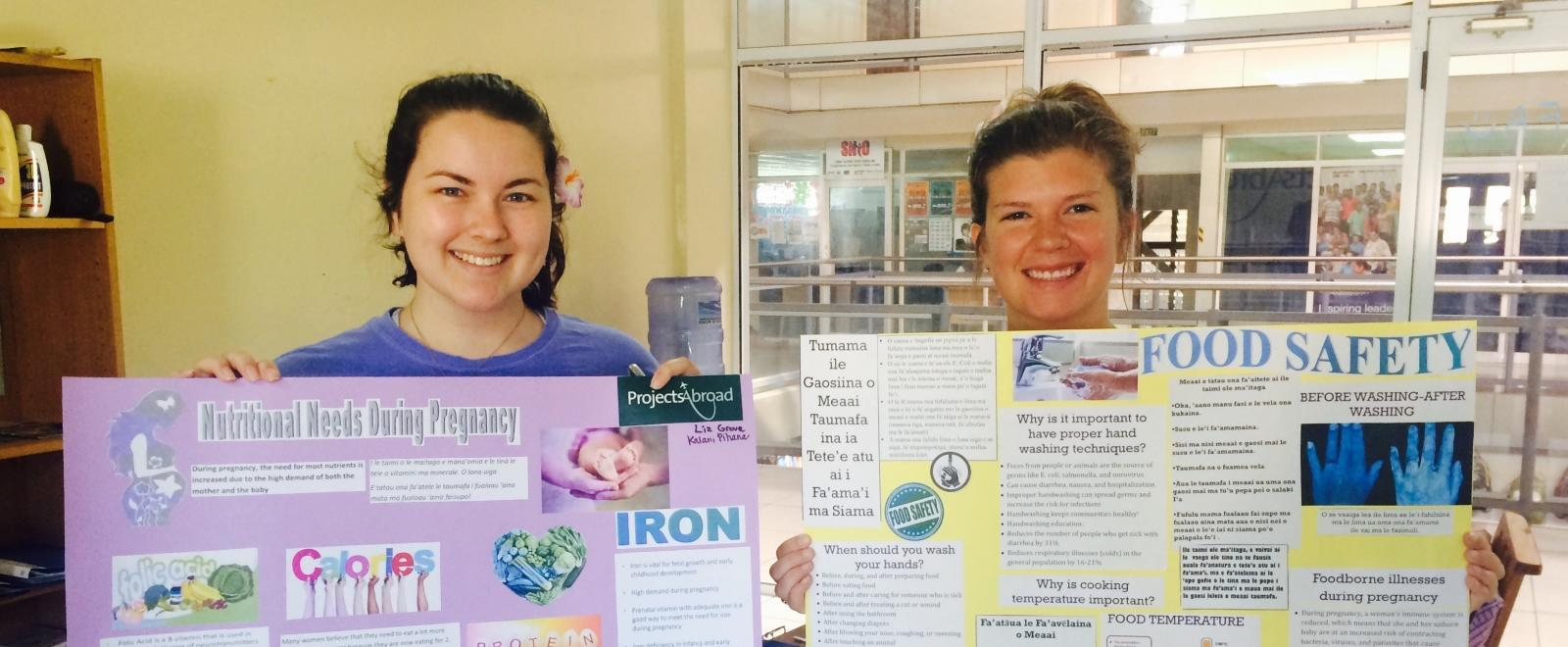 Students hold up educational posters during their Nutrition internship in Samoa.